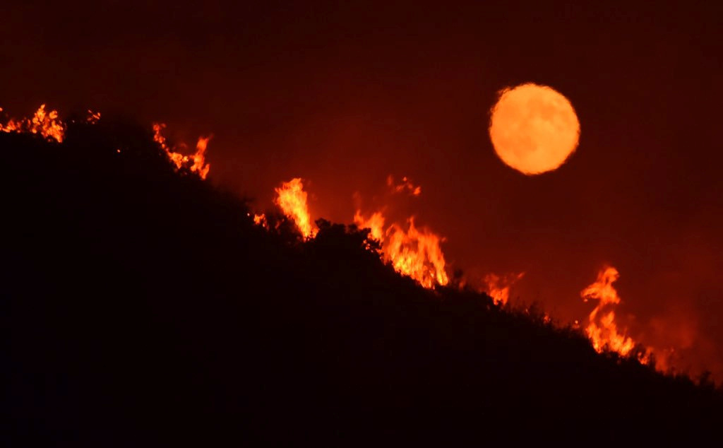 The full moon rises over flames of the Alamo fire on a hilltop off Highway 166 east of Santa Maria, California, July 7, 2017. Mike Eliason/Santa Barbara County Fire Dept/Handout via REUTERS