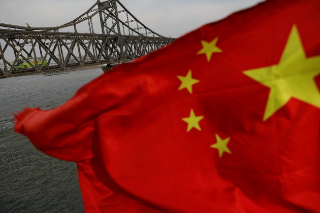 FILE PHOTO: A Chinese flag is seen in front of the Friendship bridge over the Yalu River connecting the North Korean town of Sinuiju and Dandong in China's Liaoning Province, April 1, 2017. REUTERS/Damir Sagolj/File Photo