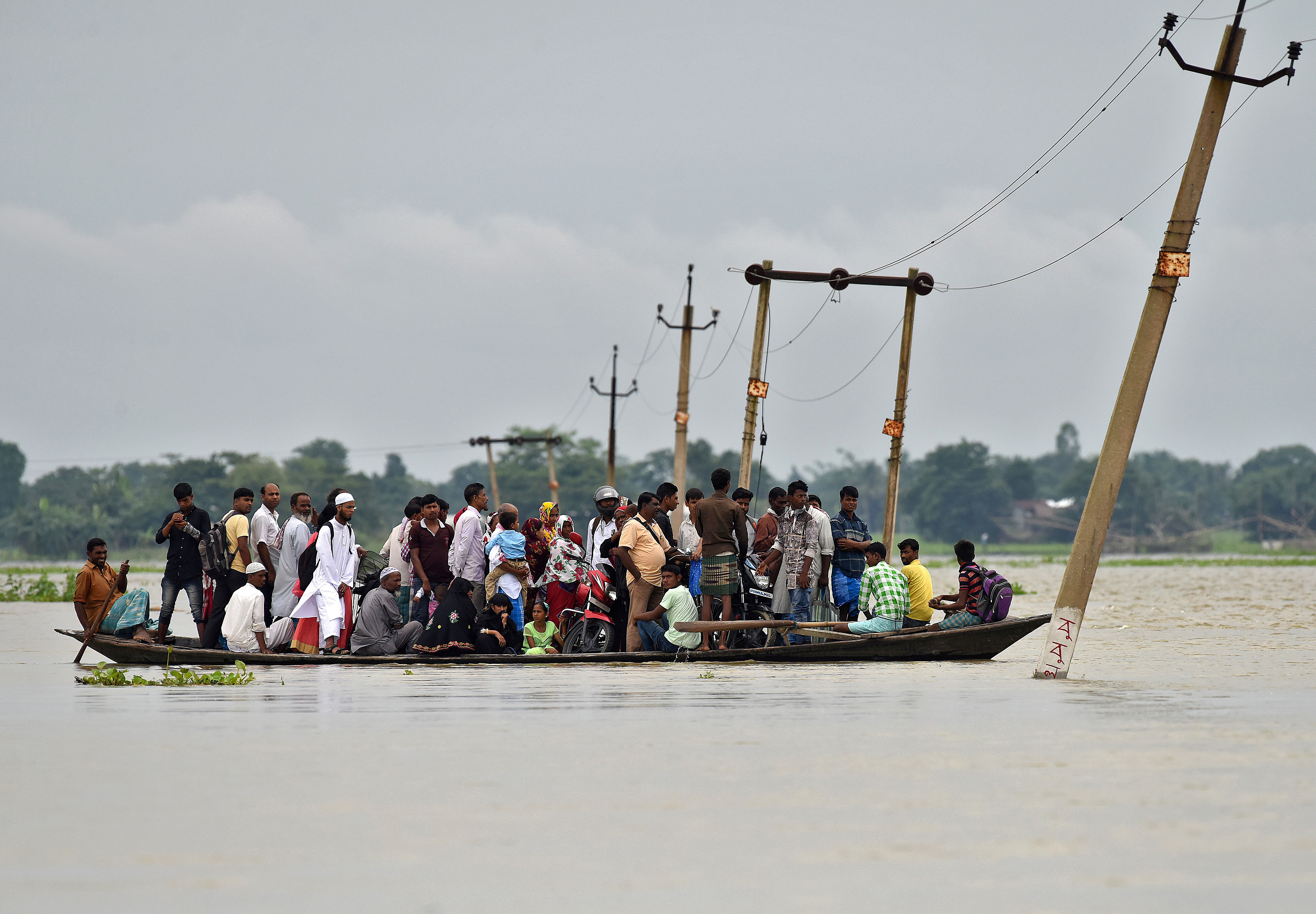 Villagers use a boat to cross a flooded road at Asigarh village in Morigaon district in Assam, India, July 4, 2017. REUTERS/Anuwar Hazarika