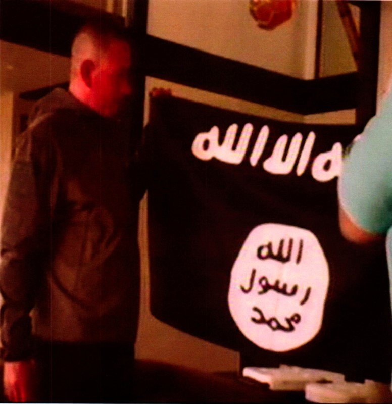 A photograph with a redacted date, and entered into federal court as an exhibit to support the government's motion to keep U.S. Army Sergeant Ikaika Erik Kang in detention without bond, shows what is described as Kang holding the Islamic State Flag after pledging allegiance to the Islamic State. Kang is charged with trying to provide material support to Islamic State extremists. the U.S. District Court for the District of Hawaii/Handout via REUTERS