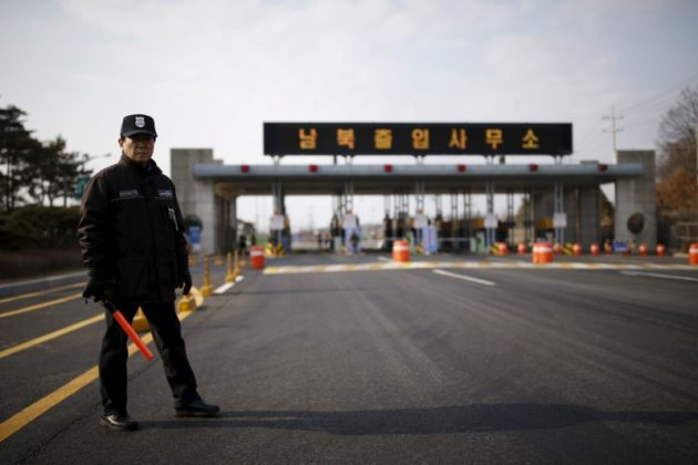 "A South Korean security guard stands guard on an empty road which leads to the Kaesong Industrial Complex (KIC) at the South's CIQ (Customs, Immigration and Quarantine), just south of the demilitarised zone separating the two Koreas, in Paju, South Korea, February 11, 2016. The Korean characters on the gateway reads ""Inter-Korean Transit Office""."
