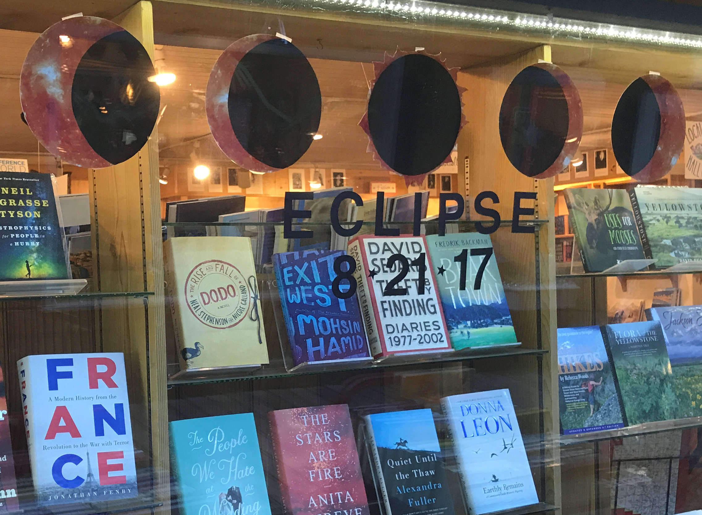 Books and a cardboard cutout representation of the moon eclipsing the sun on August 21, 2017 are seen at a bookstore in Jackson, Wyoming, U.S. July 12, 2017. Picture taken July 12, 2017. REUTERS/Ann Saphir