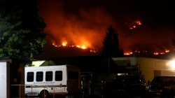 Flames from the Detwiler fire burn on a hill near the John C. Fremont Hospital in Mariposa, California, U.S., July 18, 2017. Picture taken July 18, 2017. REUTERS/Stephen Lam