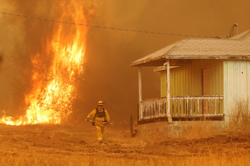 A firefighter walks near a home as flames from the fast-moving Detwiler fire approach in Mariposa, California U.S. July 19, 2017. REUTERS/Stephen Lam