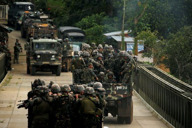 FILE PHOTO: Philippines army soldiers ride in trucks into the fighting zone as government troops continue their assault against insurgents from the Maute group in Marawi City, Philippines June 28, 2017. REUTERS/Jorge Silva