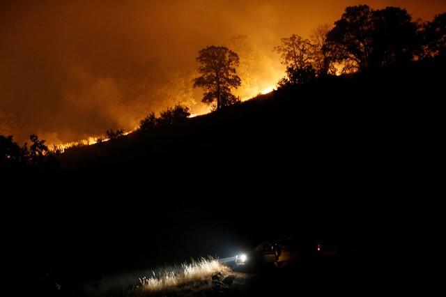 A firefighting truck is seen parked along a firebreak beneath a burning ridge during the Detwiler fire in Mariposa, California. REUTERS/Stephen Lam