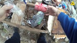 A still image captured from police body camera video appears to show a Baltimore police officer retrieving a small plastic bag in a trash-strewn yard which was placed earlier by the officer according to the Maryland Office of the Public Defender in this image released in Baltimore, Maryland, U.S. on July 19, 2017. Courtesy Baltimore Police Department/Handout via REUTERS