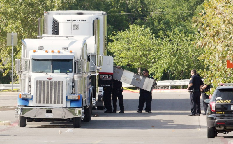 Police officers work on a crime scene after eight people believed to be illegal immigrants being smuggled into the United States were found dead inside a sweltering 18-wheeler trailer parked behind a Walmart store in San Antonio, Texas, U.S. July 23, 2017.
