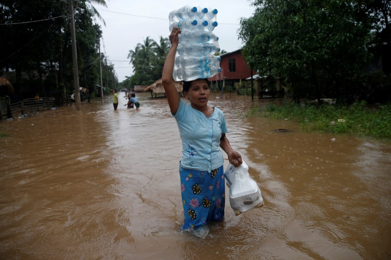 A woman carries water bottles and foods distributed by an aid organization during a flood in Kyaikto township, Mon state, Myanmar July 22, 2017.