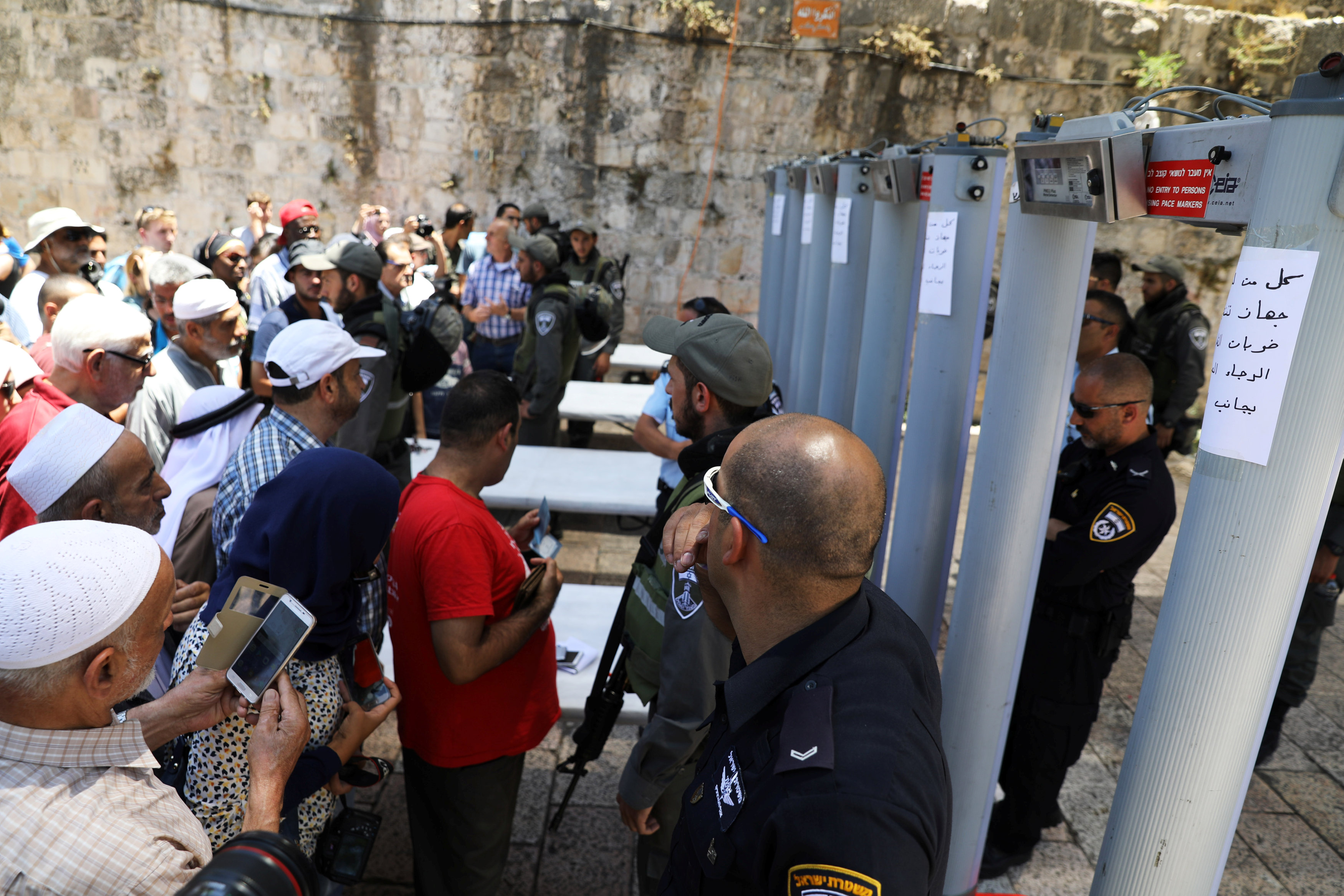 Palestinians stand in front of Israeli policemen and newly installed metal detectors at an entrance to the compound known to Muslims as Noble Sanctuary and to Jews as Temple Mount, in Jerusalem's Old City July 16, 2017.
