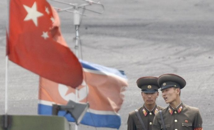 FILE PHOTO: North Korean soldiers chat as they stand guard behind national flags of China (front) and North Korea on a boat anchored along the banks of Yalu River, near the North Korean town of Sinuiju, opposite the Chinese border city of Dandong, June 10, 2013. REUTERS/Jacky Chen