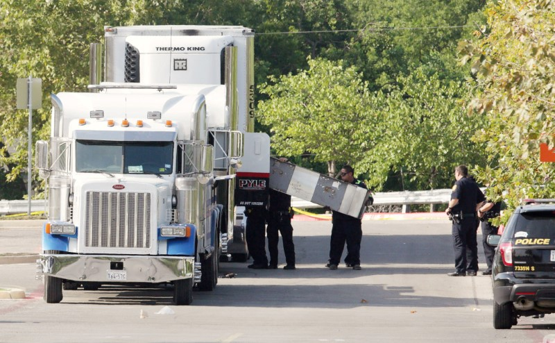 Police officers work on a crime scene after eight people believed to be illegal immigrants being smuggled into the United States were found dead inside a sweltering 18-wheeler trailer parked behind a Walmart store in San Antonio, Texas, U.S. July 23, 2017. REUTERS/Ray Whitehouse