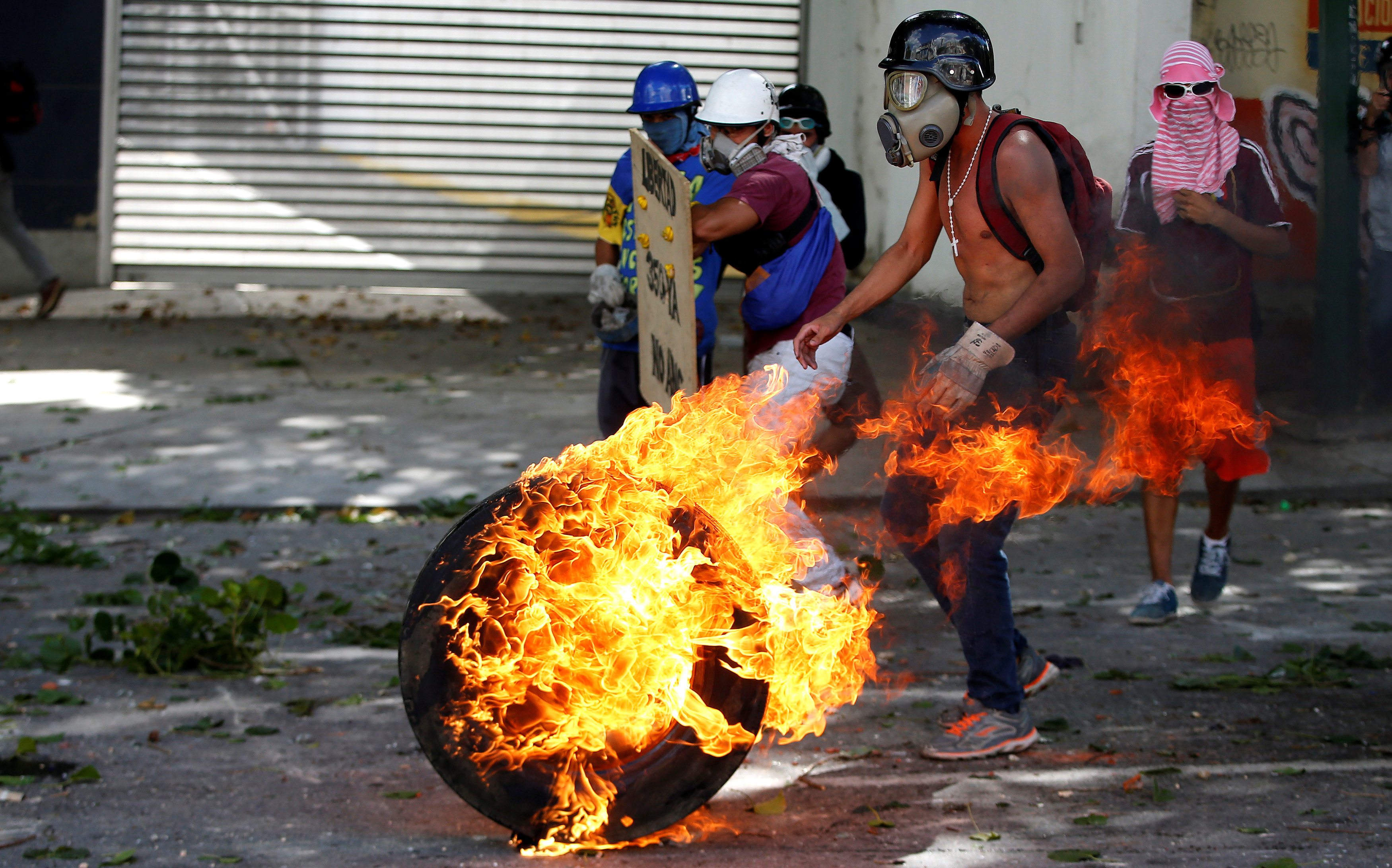 Demonstrators use a tire on fire to block a street at a rally during a strike called to protest against Venezuelan President Nicolas Maduro's government in Caracas, Venezuela July 26, 2017. REUTERS/Andres Martinez Casares