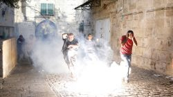 Palestinians react as a stun grenade explodes in a street at Jerusalem's Old city outside the compound known to Muslims as Noble Sanctuary and to Jews as Temple Mount, after Israel removed all security measures it had installed at the compound. REUTERS/Amir Cohen