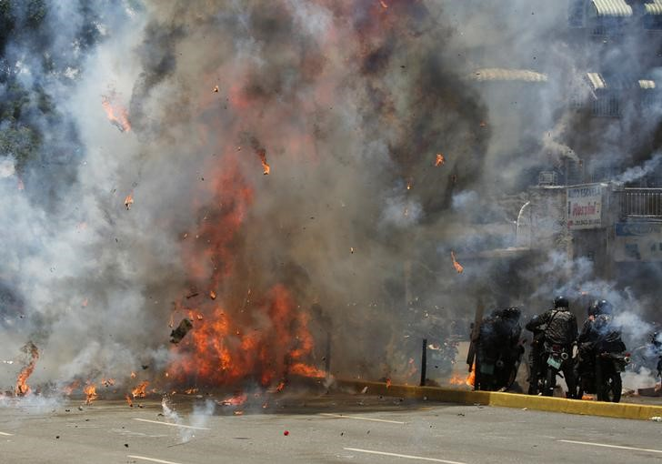 Flames erupt as clashes break out near security forces members (R) while the Constituent Assembly election is being carried out in Caracas, Venezuela,