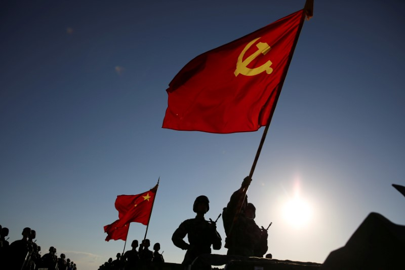 Soldiers carry a PLA flag and Chinese national flags before the military parade to commemorate the 90th anniversary of the foundation of China's People's Liberation Army (PLA) at Zhurihe military base in Inner Mongolia Autonomous Region, China, July 30, 2017. REUTERS/Stringer