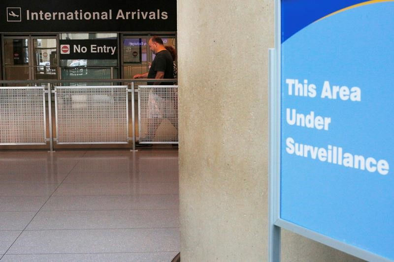 A sign warns of surveillance at the International Arrival area at Logan Airport in Boston.