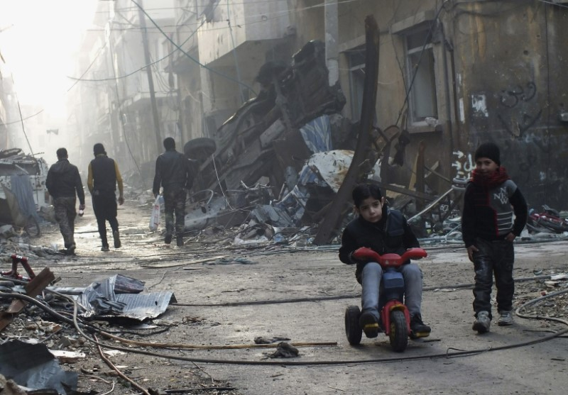 A boy rides on a tricycle along a damaged street in the besieged area of Homs,