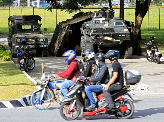 Motorists drive past an Armoured Personnel Carrier (APC) parked near the venue of the 50th ASEAN Foreign Ministers meeting in Pasay city, metro Manila, Philippines August 4, 2017.