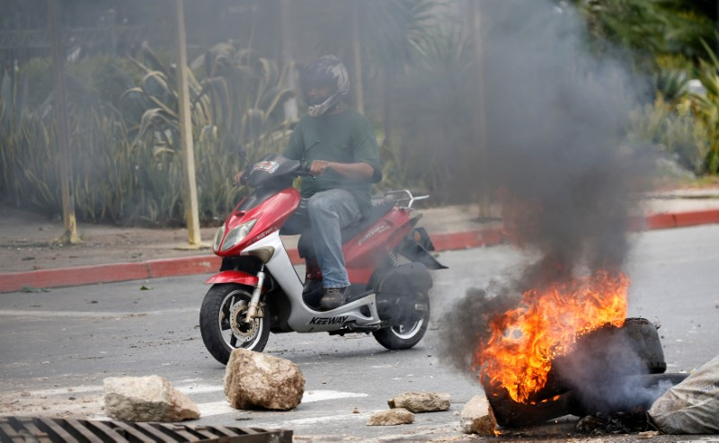Motorcyclist passes through a barricade during protest against Venezuela's President Nicolas Maduro's government in Valencia, Venezuela August 6, 2017.