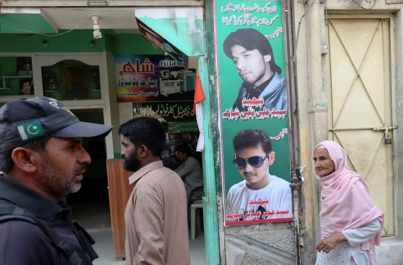 A policeman (L) and residents walk past a shop displaying the pictures of men, who were killed in a suicide blast on January 2015,