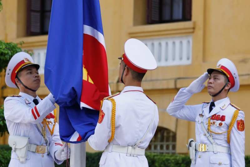Honour guards raise an Association of Southeast Asian Nations (ASEAN) flag at a flag-raising ceremony to mark the 50th anniversary of the regional group at Vietnam's Ministry of Foreign Affairs in Hanoi August 8, 2017. REUTERS/Kham