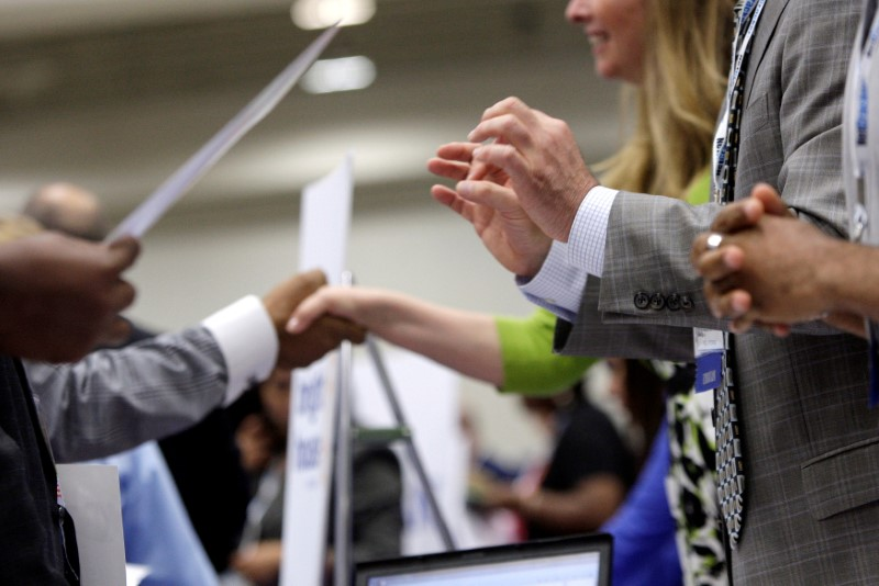FILE PHOTO: Corporate recruiters (R) gesture and shake hands as they talk with job seekers in Washington, June 11, 2013. REUTERS/Jonathan Ernst/File Photo