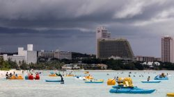Tourists frolic on the waters overlooking posh hotels in Tumon tourist district.