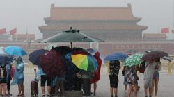 Tourists hold umbrellas as they visit Tiananmen Square during a rainstorm in Beijing, China August 12, 2017. REUTERS/Stringer