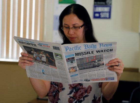 A hotel receptionist reads a local newspaper in Tamuning, Guam, a U.S. Pacific Territory, August 12, 2017. REUTERS/Erik De Castro
