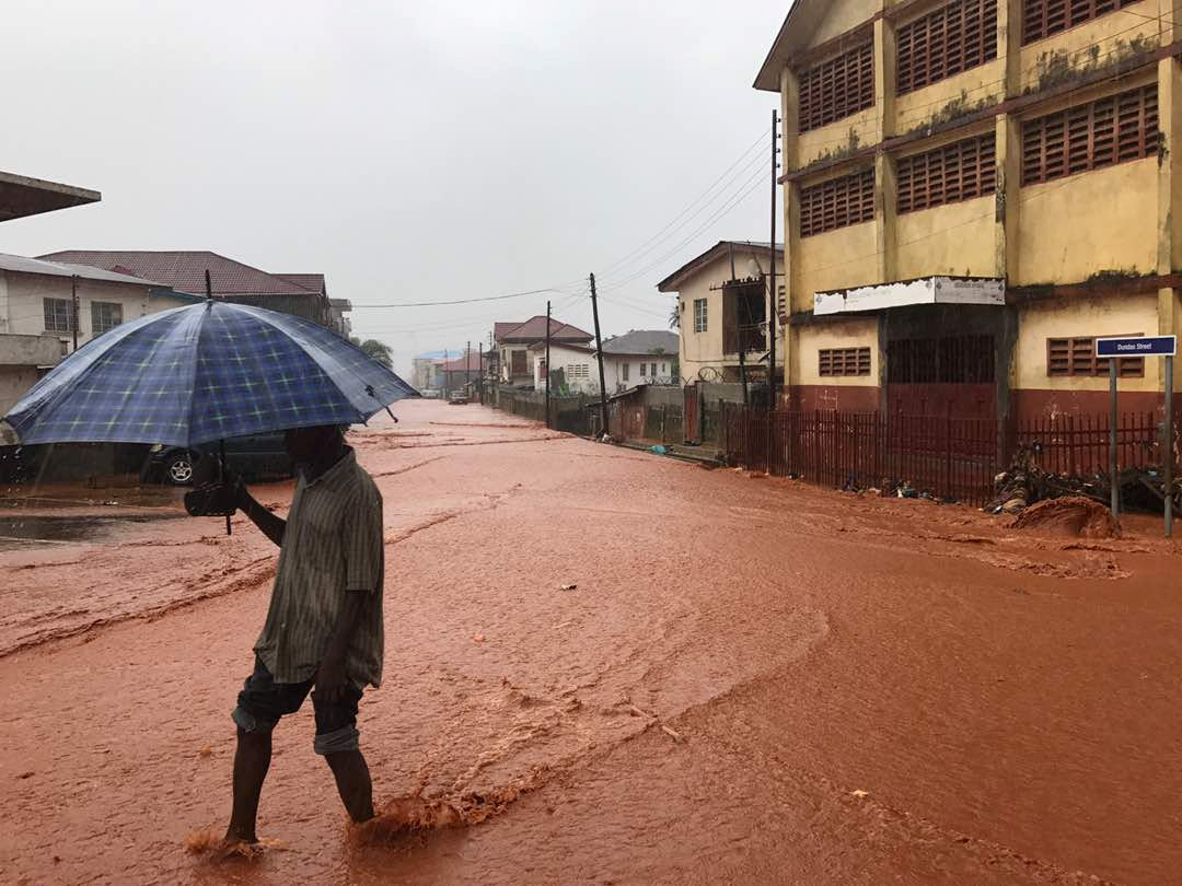 A man walks under umbrella in water covered street in Freetown, Sierra Leone August 14, 2017 in this picture obtained from social media.