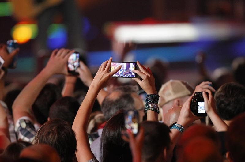 FILE PHOTO: A fan uses a cell phone to record a performance during the 2014 CMT Music Awards in Nashville, Tennessee June 4, 2014. REUTERS/Harrison McClary