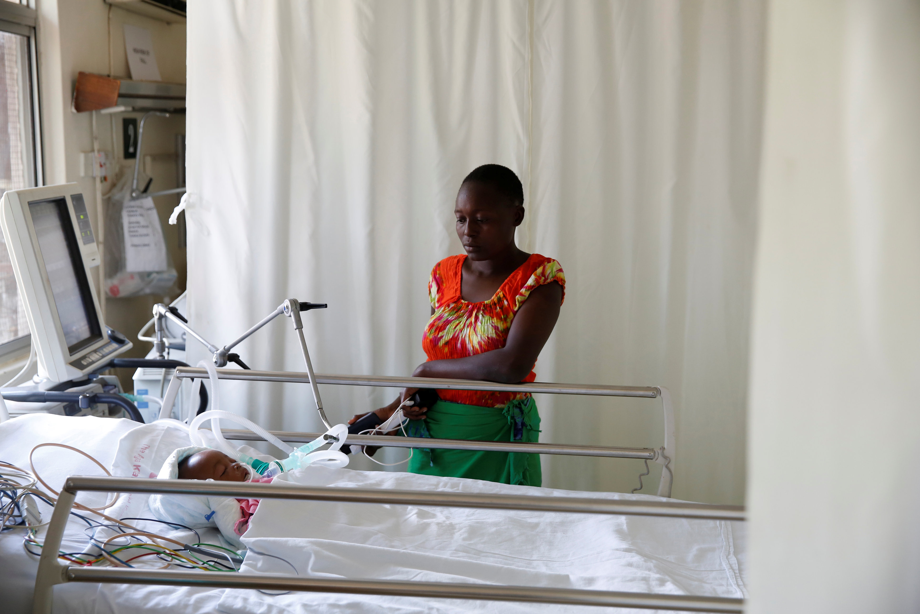 Lenzer, mother of six month-old Samantha Pendo, stands next to her bed as the girl remains in critical condition in the Intensive Care Unit of Aga Khan Hospital in Kisumu, Kenya August 14, 2017. REUTERS/Baz Ratner