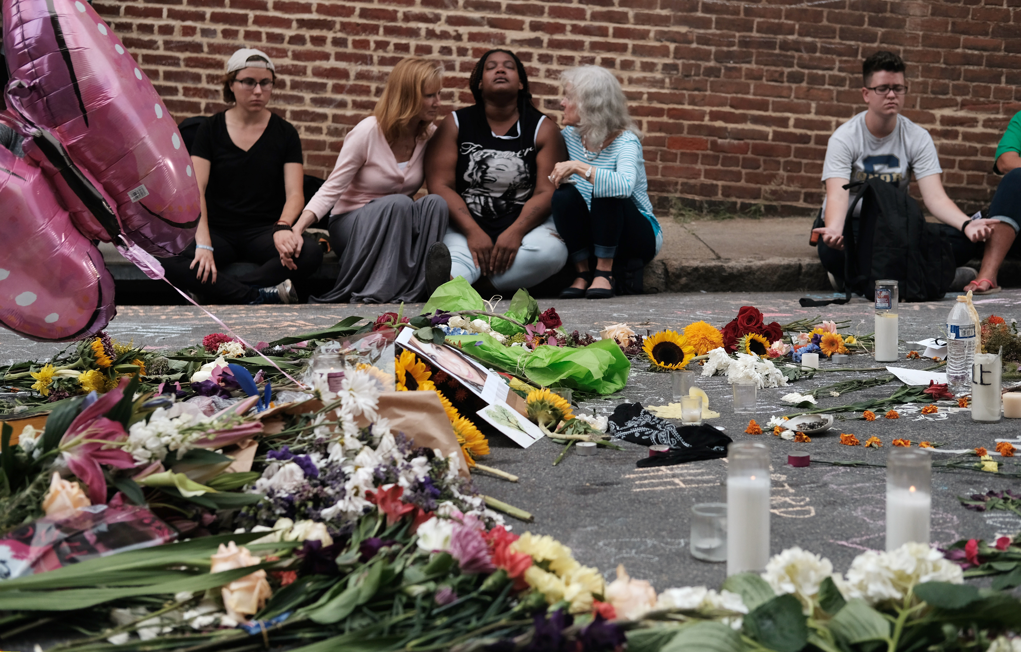 "Women sit by an impromptu memorial of flowers commemorating the victims at the scene of the car attack on a group of counter-protesters during the ""Unite the Right"" rally as people continue to react to the weekend violence in Charlottesville, Virginia. REUTERS/Justin Ide"