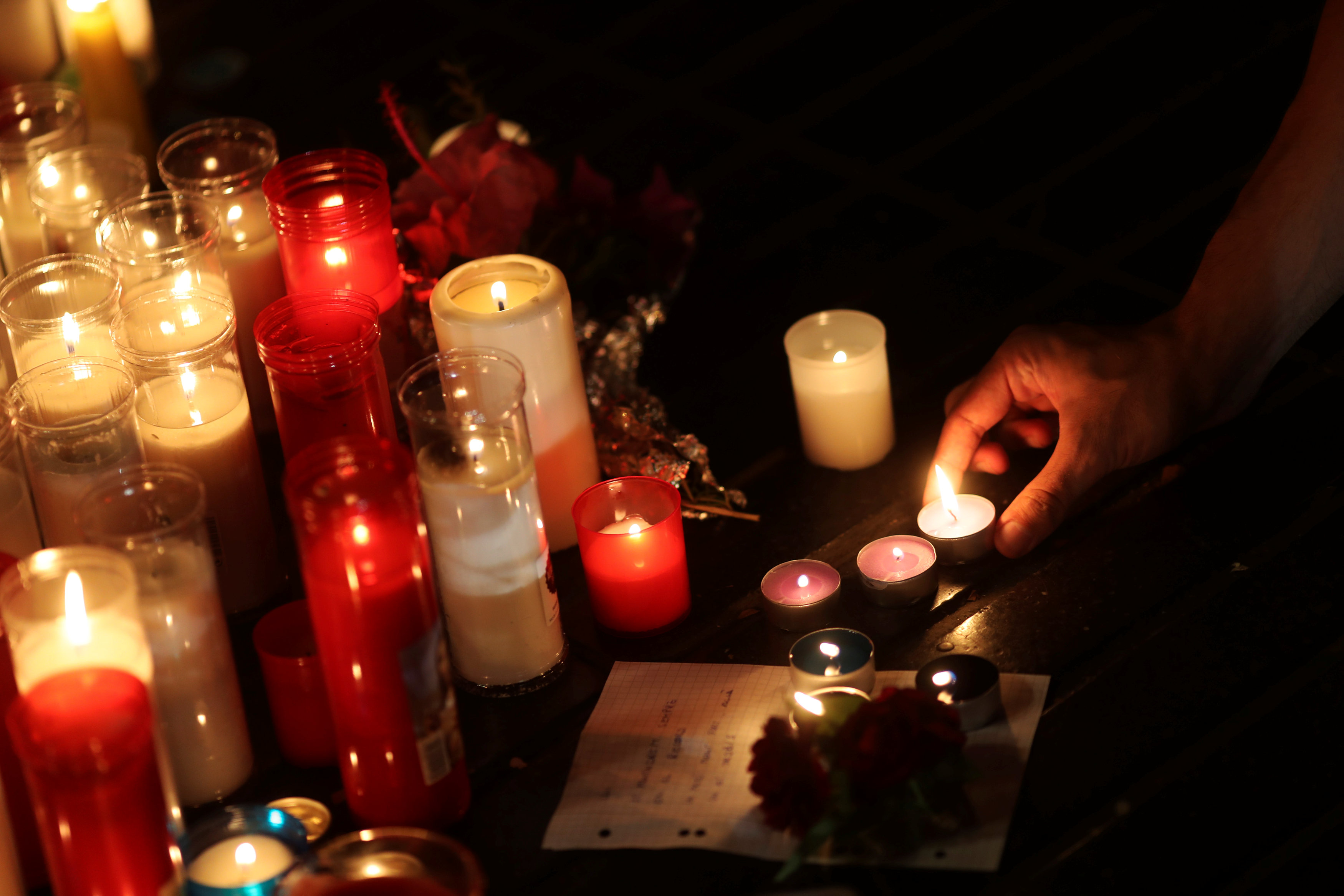 A man lights a candle at an impromptu memorial where a van crashed into pedestrians at Las Ramblas in Barcelona, Spain, August 19, 2017