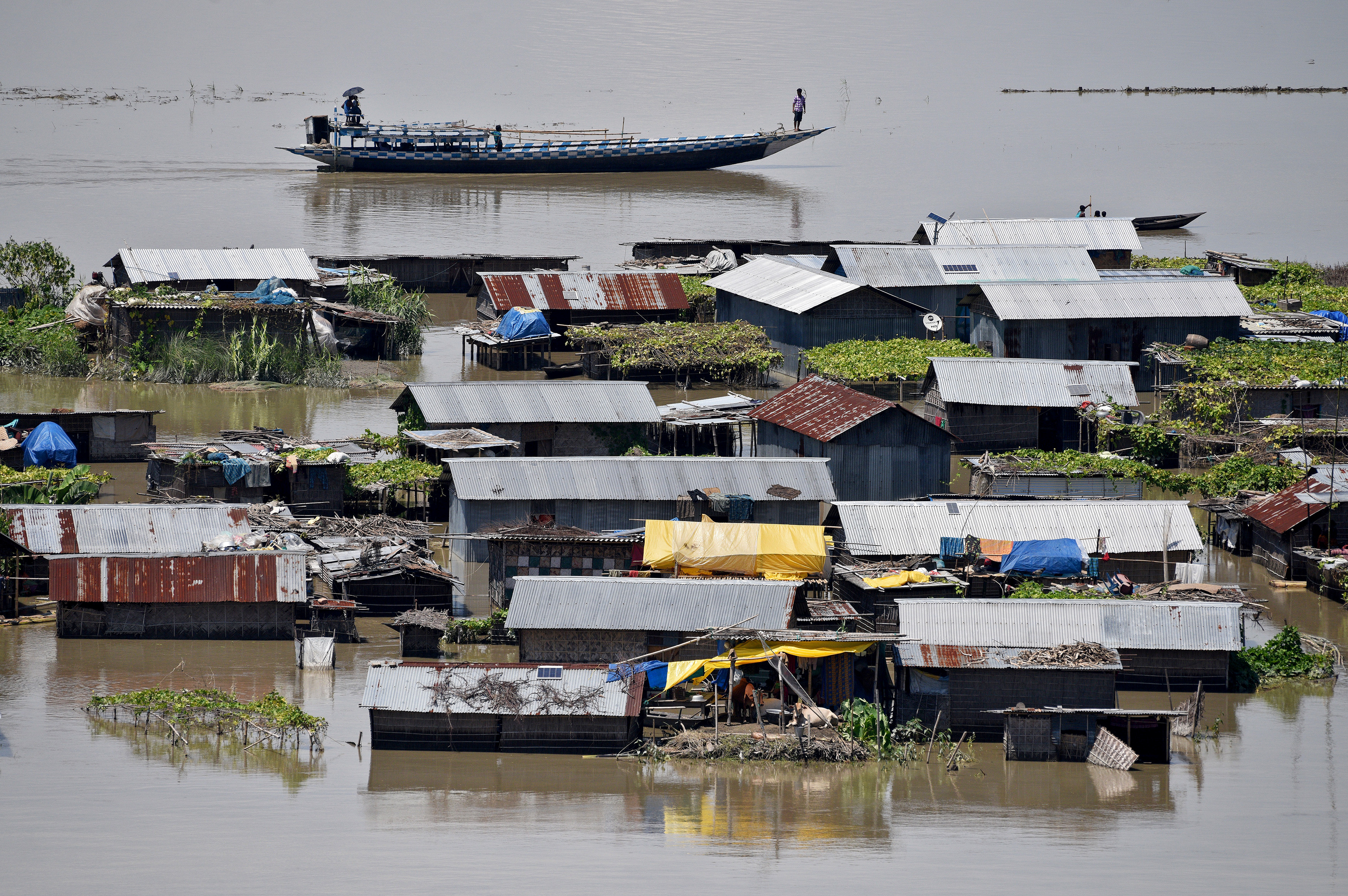 Villagers use a boat as they row past partially submerged houses at a flood-affected village in Morigaon district in Assam,