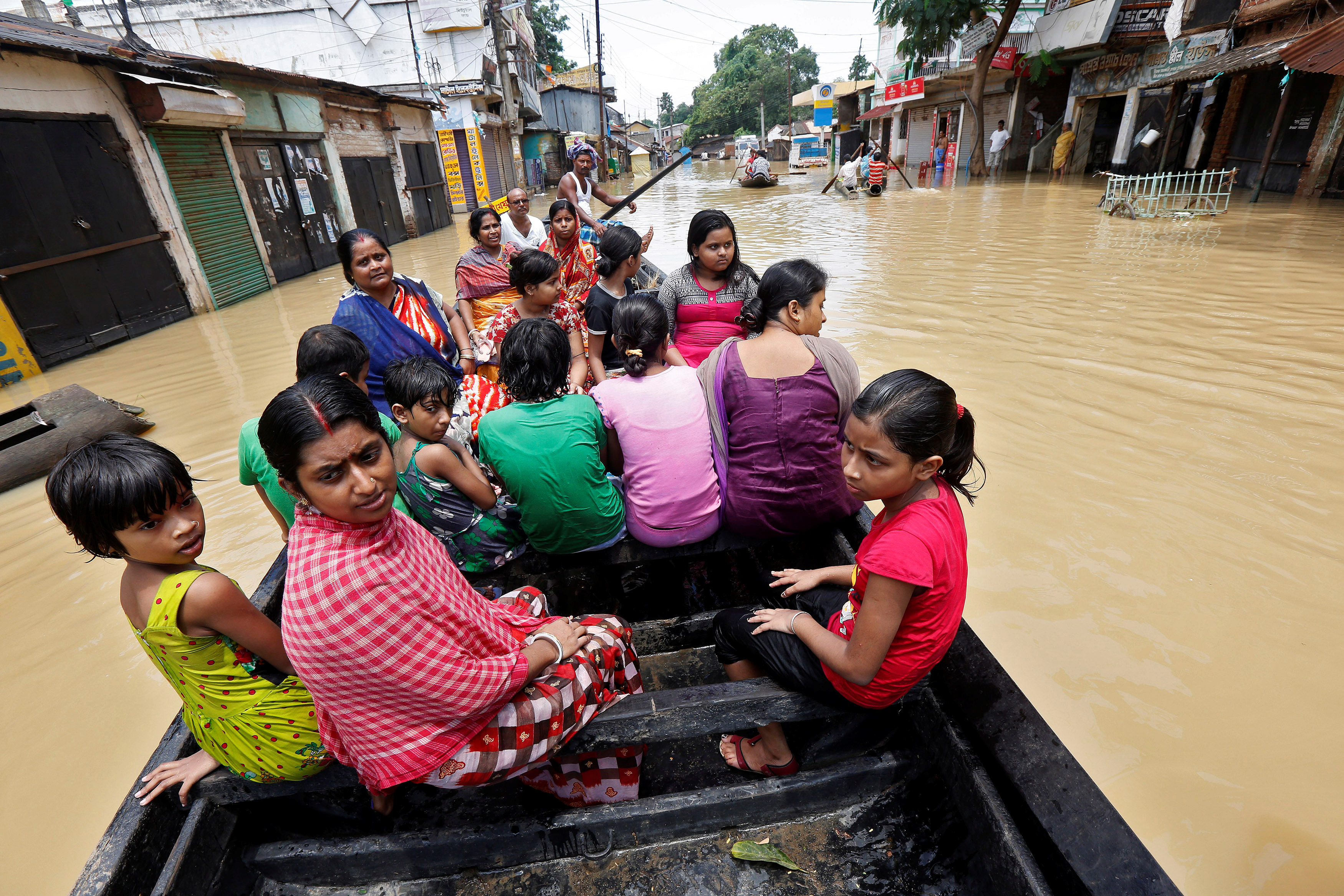 People use a boat as they try to move to safer places along a flooded street in West Midnapore district, in West Bengal