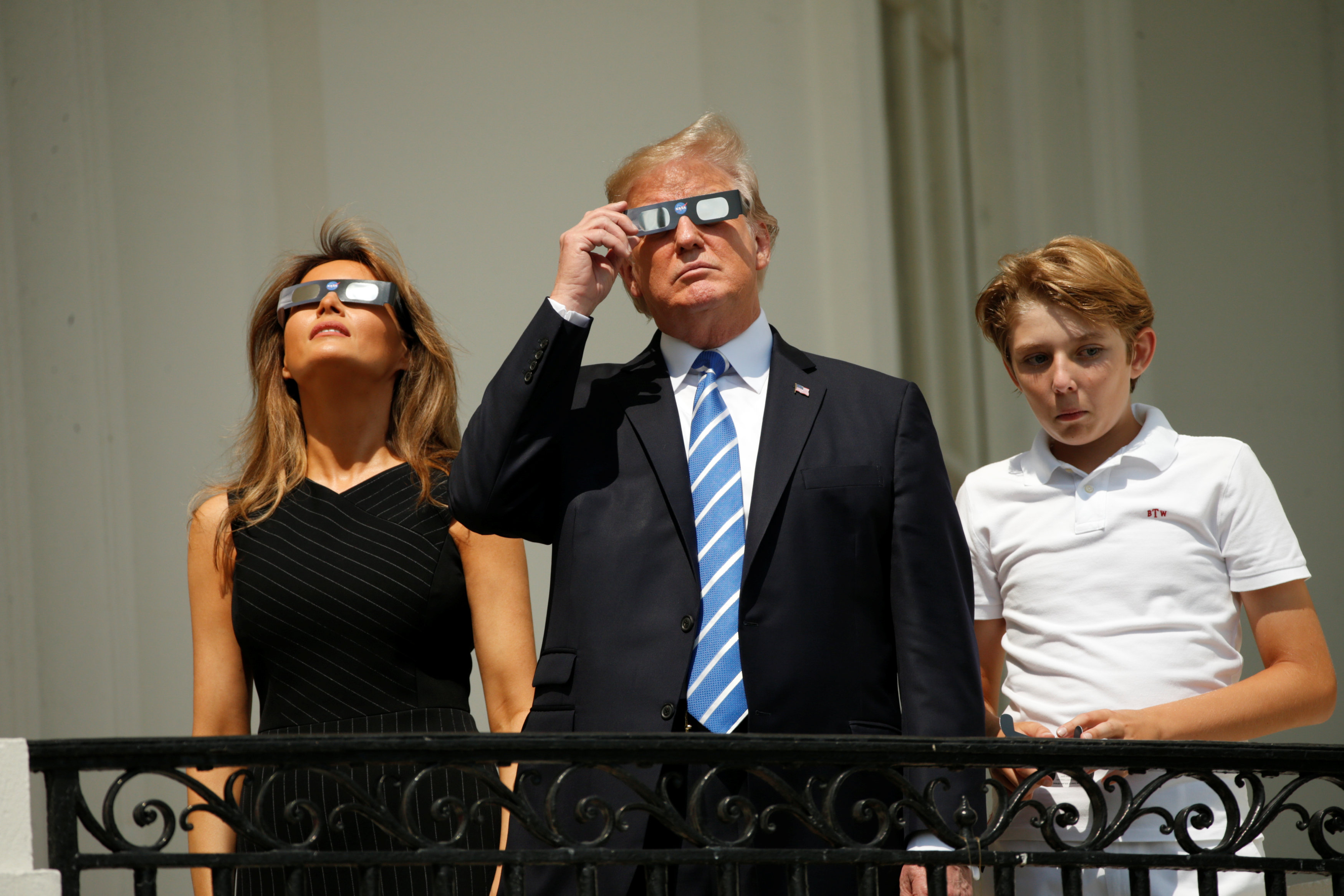U.S. President Donald Trump watches the solar eclipse with first Lady Melania Trump and son Barron from the Truman Balcony at the White House in Washington, U.S., August 21, 2017. REUTERS/Kevin Lamarque