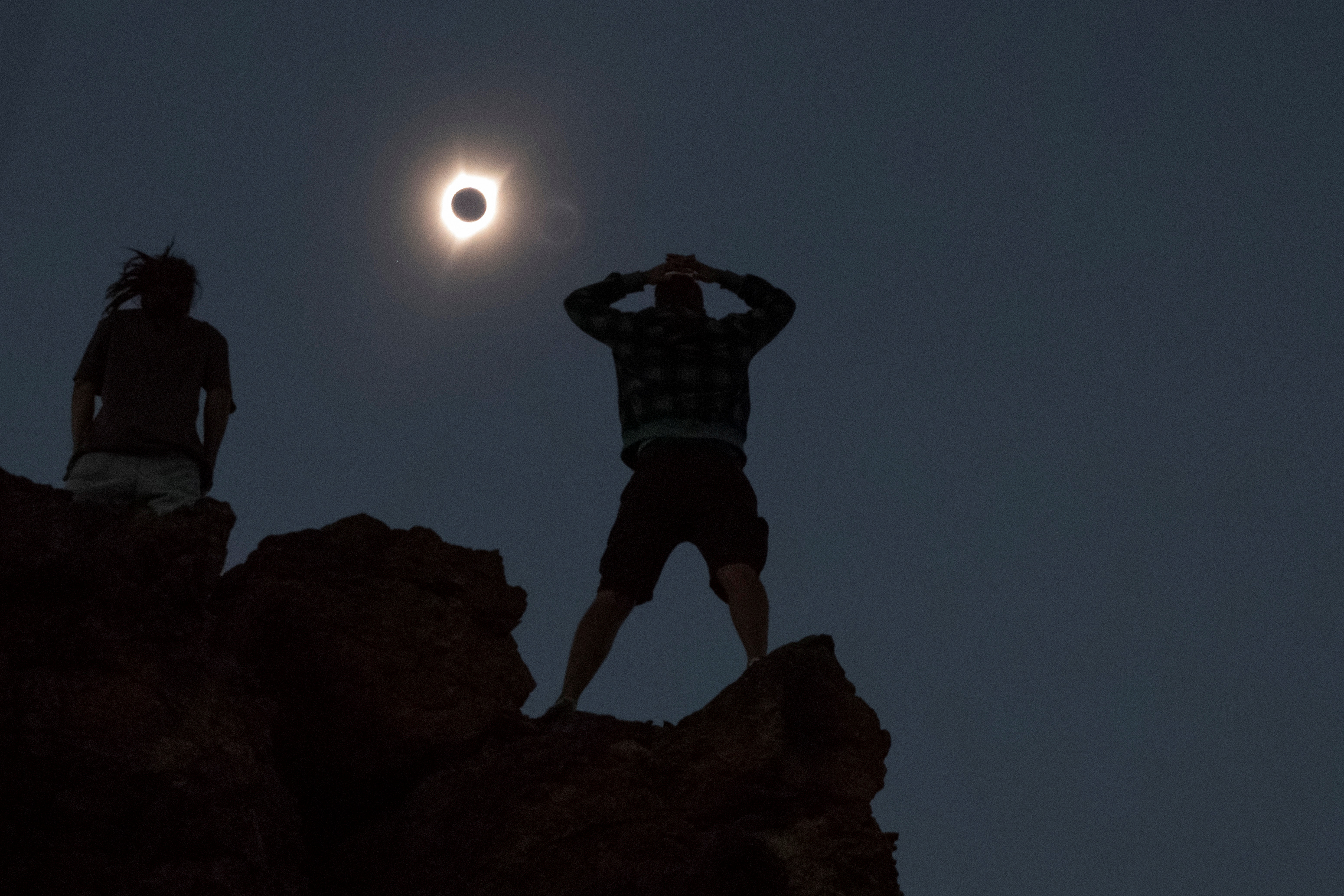 Enthusiasts Tanner Person (R) and Josh Blink, both from Vacaville, California, watch a total solar eclipse while standing atop Carroll Rim Trail at Painted Hills, a unit of the John Day Fossil Beds National Monument, near Mitchell, Oregon, U.S. August 21, 2017. Location coordinates for this image is near 44°39'117'' N 120°6'042'' W. REUTERS/Adrees Latif