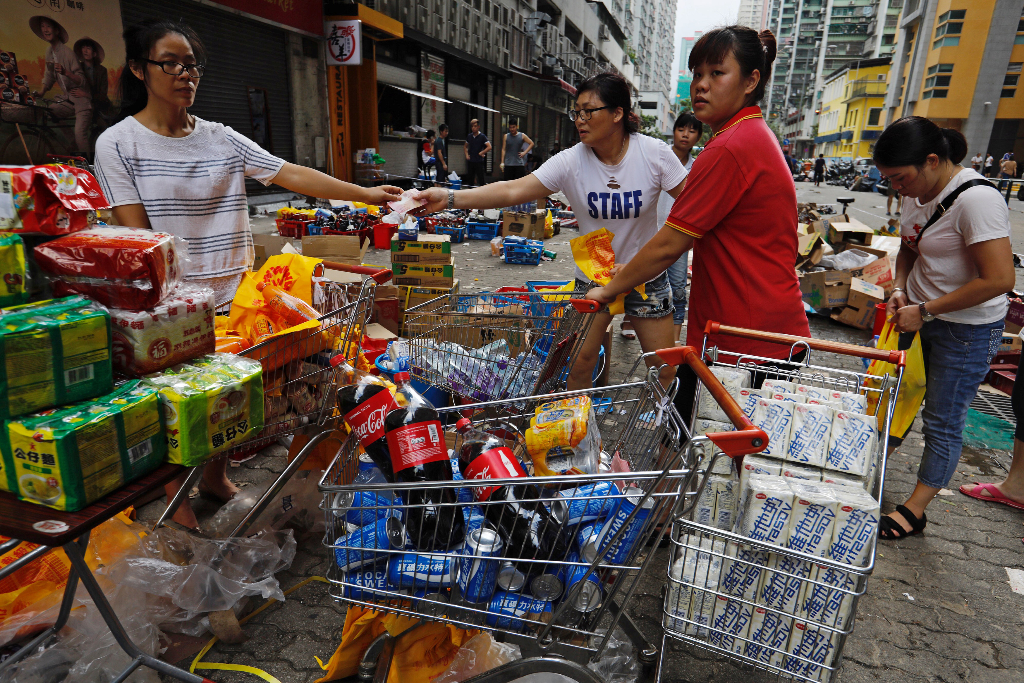 Supermarket staff sell goods outside a supermarket during power outages after Typhoon Hato hit in Macau, China August 24, 2017. REUTERS/Tyrone Siu