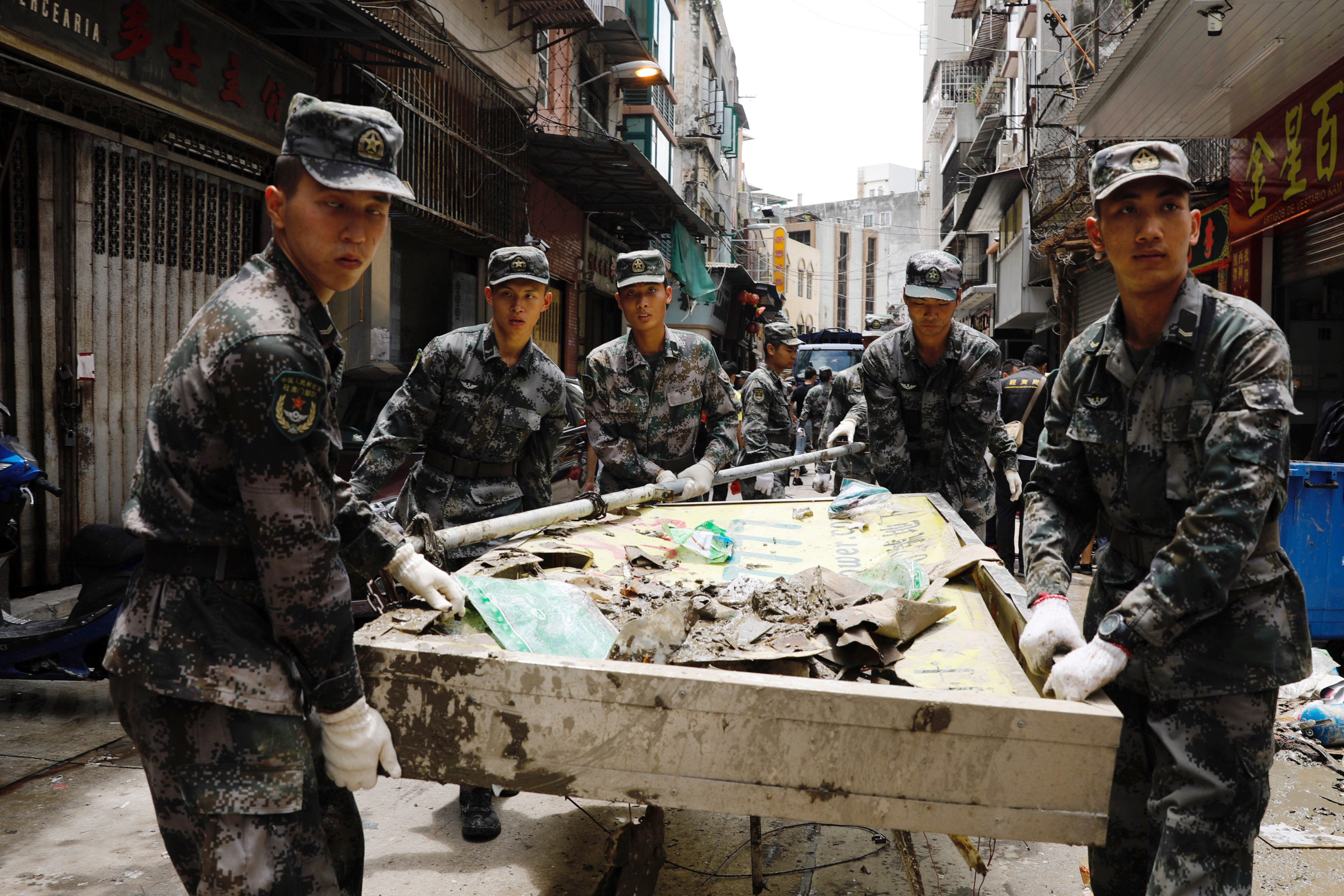 People's Liberation Army (PLA) soldiers clean debris after Typhoon Hato hits in Macau, China August 25, 2017. REUTERS/Tyrone Siu