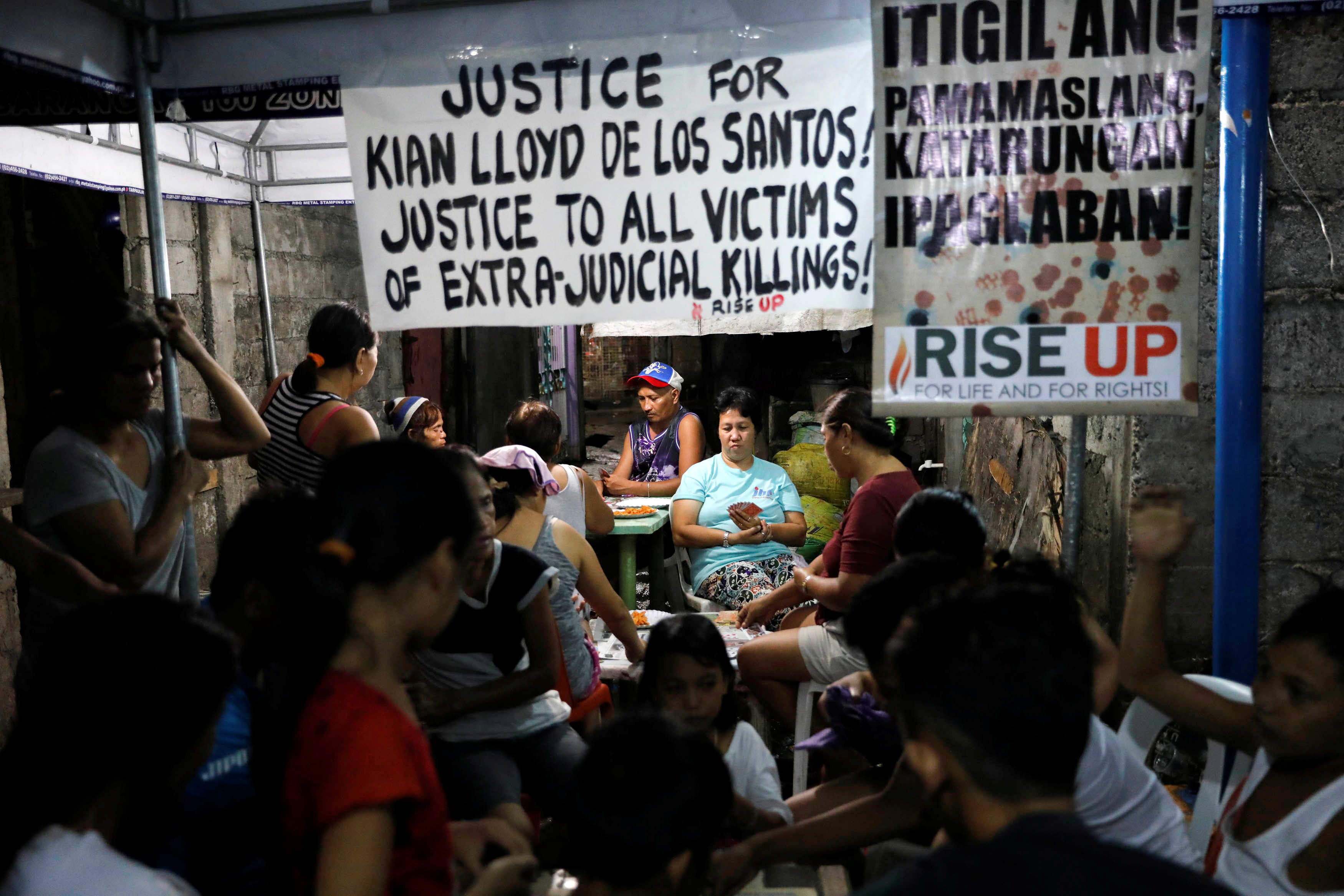 Neighbours play cards at the wake of Kian delos Santos, a 17-year-old student who was shot during anti-drug operations in Caloocan, Metro Manila, Philippines August 22, 2017. REUTERS/Dondi Tawatao