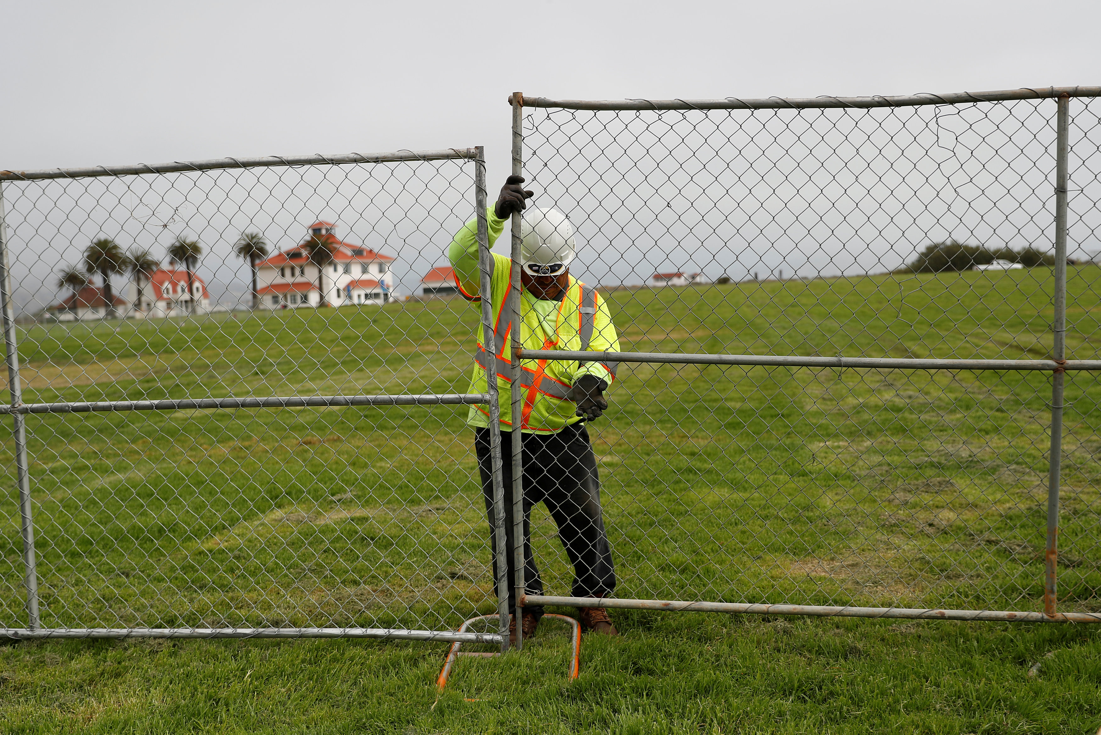 A worker installs a fence at Crissy Field in anticipation of Saturday's Patriot Prayer rally and counter demonstration in San Francisco, California, U.S. August 25, 2017. REUTERS/Stephen Lam