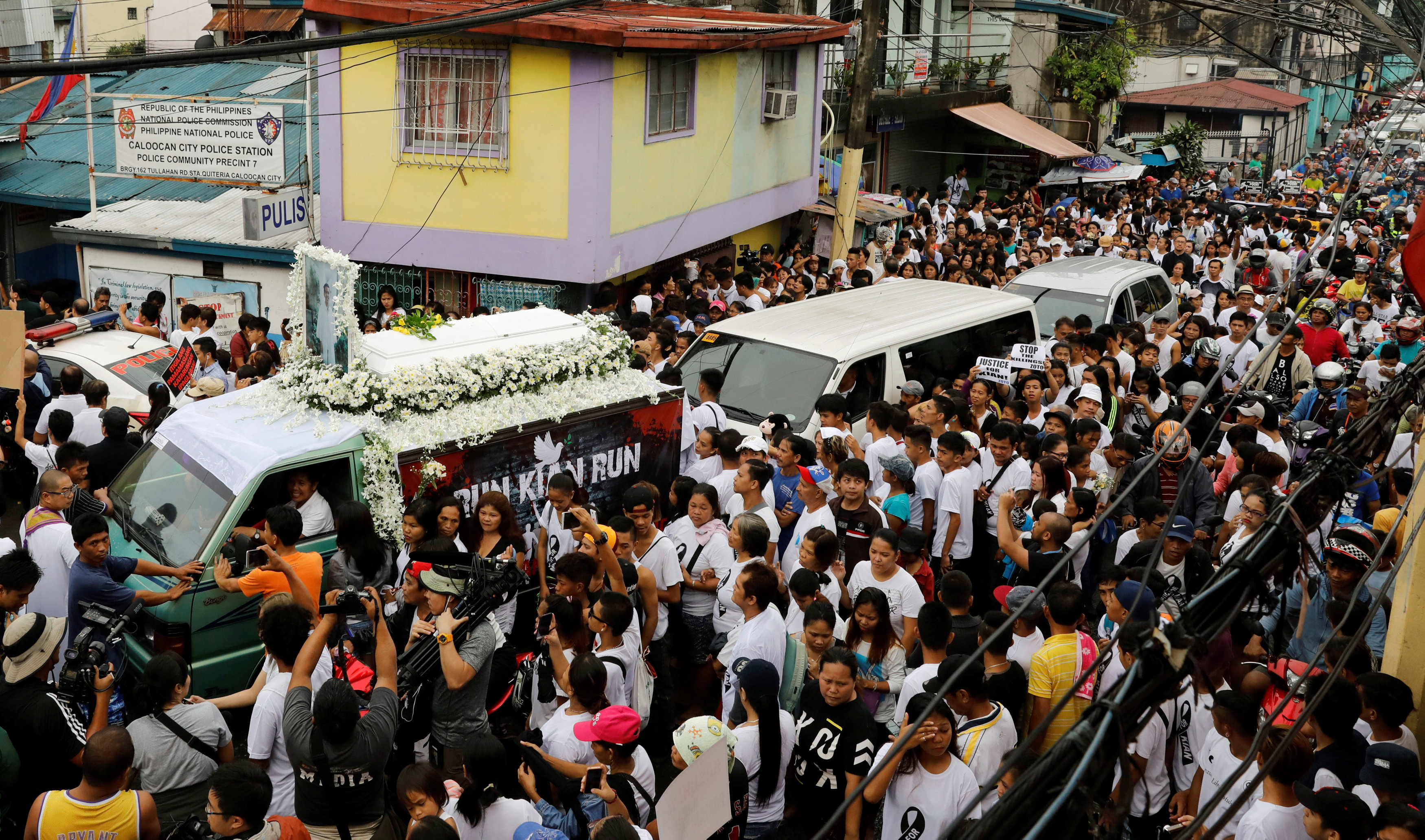 The flower-decked hearse of Kian delos Santos, a 17-year-old student who was shot during anti-drug operations, stops in front of a police station during the funeral march in Caloocan, Metro Manila, Philippines August 26, 2017. REUTERS/Erik De Castro