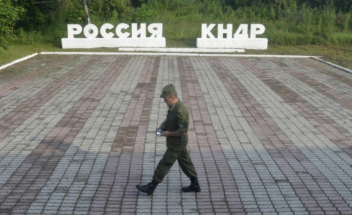 """A guard walks along a platform past signs, which read """"Russia"""" (L) and """"DPRK""""(Democratic People's Republic of Korea), at the border crossing between Russia and North Korea in the settlement of Tumangan, North Korea July 18, 2014."""