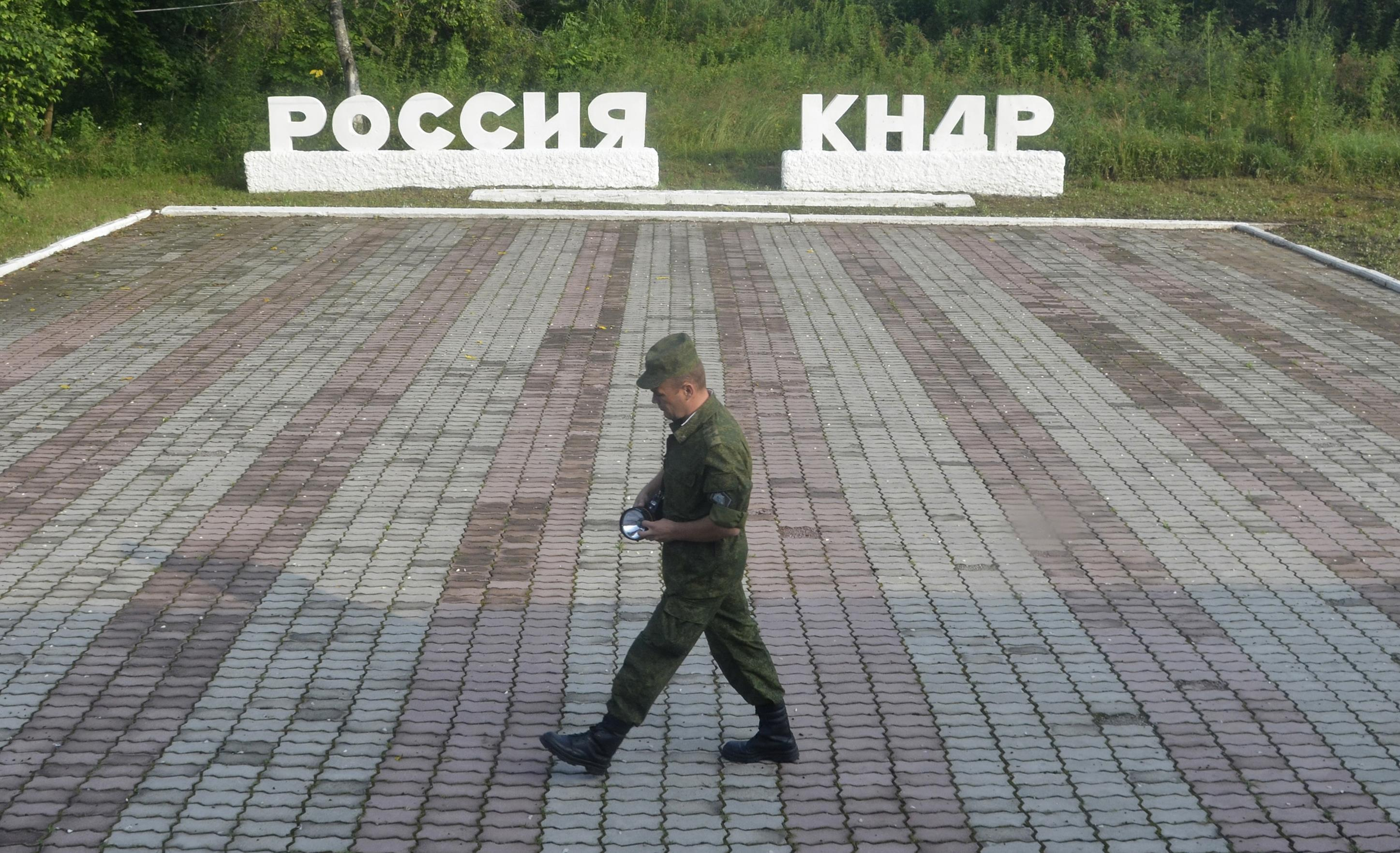 "A guard walks along a platform past signs, which read ""Russia"" (L) and ""DPRK""(Democratic People's Republic of Korea), at the border crossing between Russia and North Korea in the settlement of Tumangan, North Korea July 18, 2014."