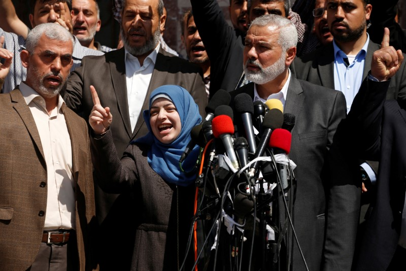 Hamas Chief Ismail Haniyeh (R) and Hamas Gaza leader Yehya Al-Sinwar (L) attend a news conference as the wife of slain senior Hamas militant Mazen Fuqaha gestures, in Gaza City May 11, 2017.