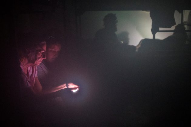 Women are illuminated by the light of a smart phone as they seek refuge in the Good Samaritan Rescue Mission in Corpus Christi.