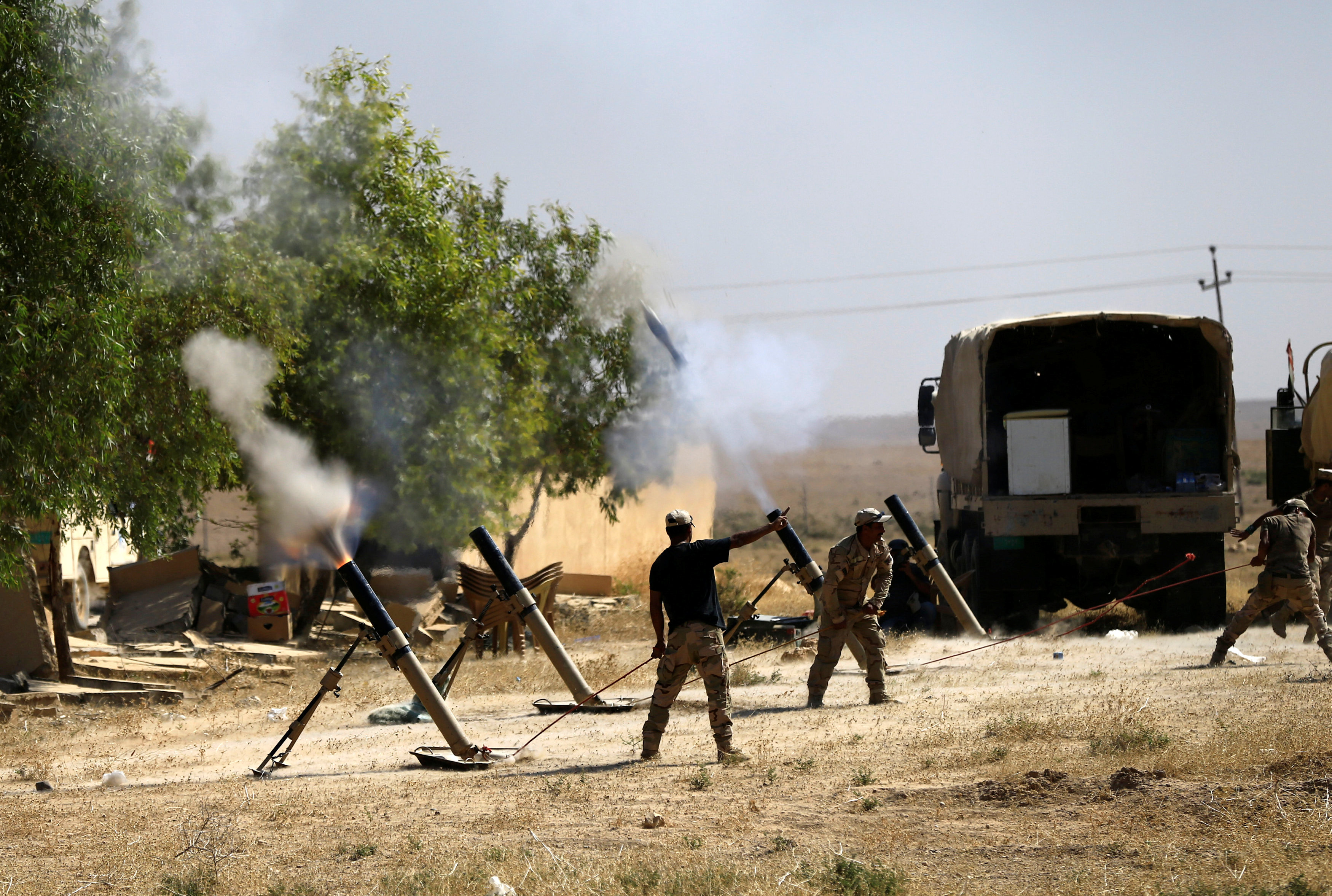 Members of Iraqi Army fire mortar shells during the war between Iraqi army and Shi'ite Popular Mobilization Forces (PMF) against the Islamic State militants in al-Ayadiya, northwest of Tal Afar, Iraq August 28, 2017. REUTERS/Thaier Al-Sudani