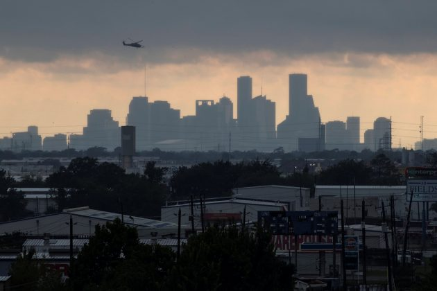 A helicopter hovers above the Houston skyline as sunlight breaks through storm clouds from Tropical Storm Harvey in Texas, U.S. August 29, 2017. REUTERS/Adrees Latif